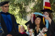 Zanette Johnson receives her doctoral hood from Professor Shelley Goldman with Dean Claude Steele looking on.