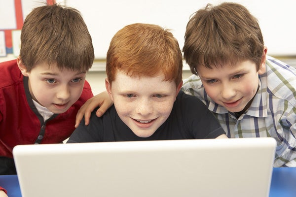 Three school-age boys looking at a laptop computer
