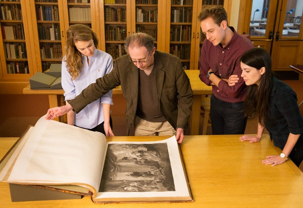 Professor Stephen Orgel opens the magnificently illustrated Boydell Shakespeare 'elephant folio,' from the Stanford Libraries's collection while, from left, senior Meredith Colton, and graduate students Luke Barnhart and Jessica Beckman, at right, look on