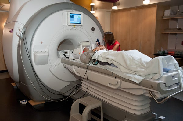 fMRI machine with subject and researcher