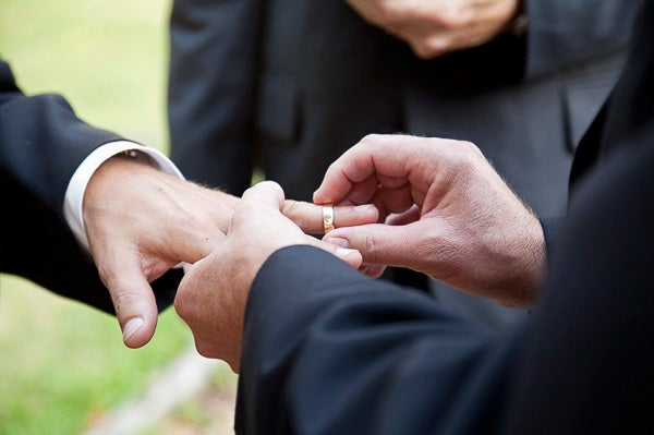 One groom putting a ring on the finger of another in a same-sex marriage