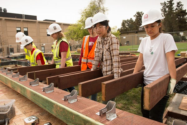 Stanford students from right, Erica Levine, Yoo-Yoo Yeh, Claire Frykman and classmates prepare to place floor joists that will support a deck at the Start.Home.