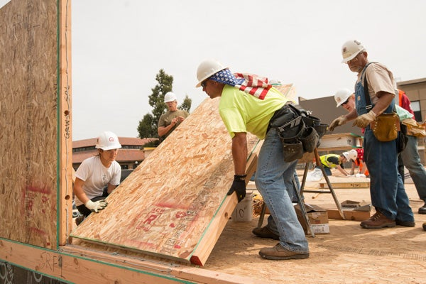 Student Erica Levine, left, works with Craig Triplett, a mentor from the United Brotherhood of Carpenters, to set a panel from the first wall to be constructed on the solar-powered house.