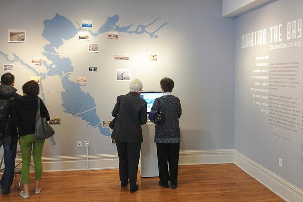 Visitors explore the Year of the Bay virtual history map at the California Historical Society exhibition 'Curating the Bay.'