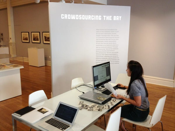 A Year of the Bay project officer scans and pins historical postcards at the California Historical Society exhibition.