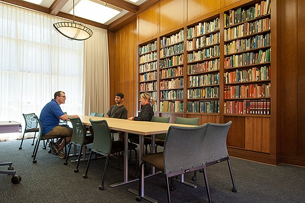 Aaron Shkuda, assistant director of ITALIC, meets with student staff members in the recently renovated library in Burbank dormitory.