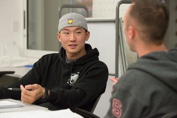Jonathan Kong, left, and Ryan Cotter, who both served in the Navy, engage in a discussion during their academic research writing course.
