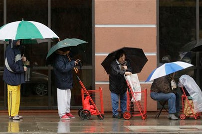People take cover from the rain in San Francisco / AP Photo/Eric Risberg