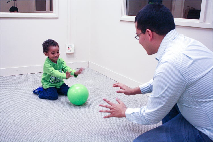 Researcher rolling a ball to a toddler