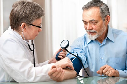 doctor measuring patient's blood pressure / Alexander Raths/Shutterstock