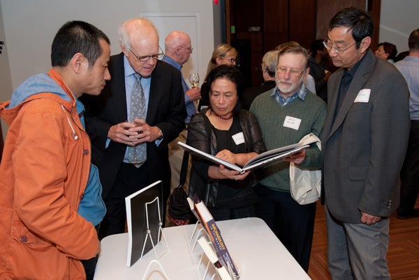 People admiring books at Stanford Humanities Center celebration