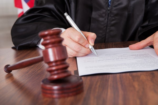 Judge signing paper with gavel visible in front