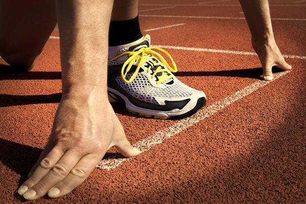 Foot and hands of runner on track