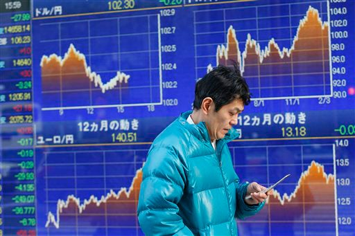 A man uses a mobile phone in front of a securities firm's electronic stock board in Tokyo on Feb. 24, 2014.