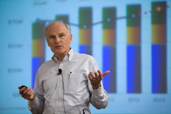 Tim Warner speaking in front of a large graphic