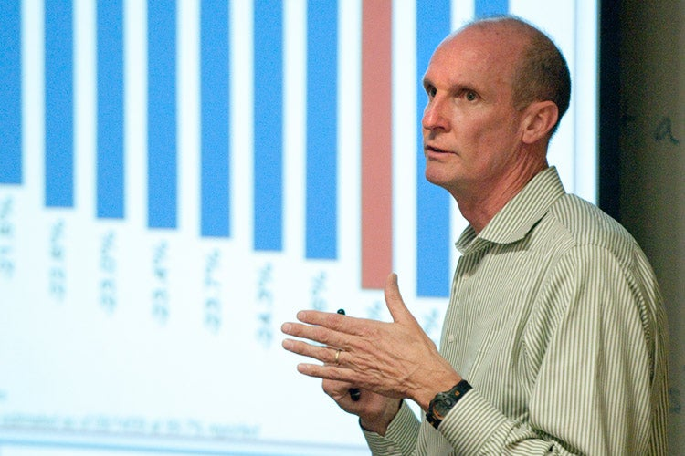 John Powers standing in front of a screen showing a graph.