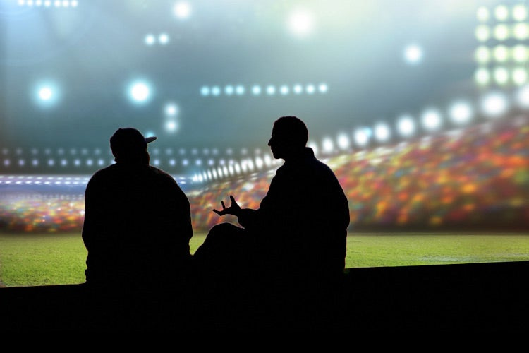 silhouette of people talking at a stadium