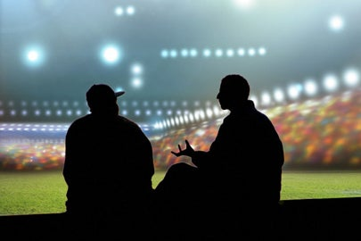 silhouette of people talking at a stadium / Shutterstock