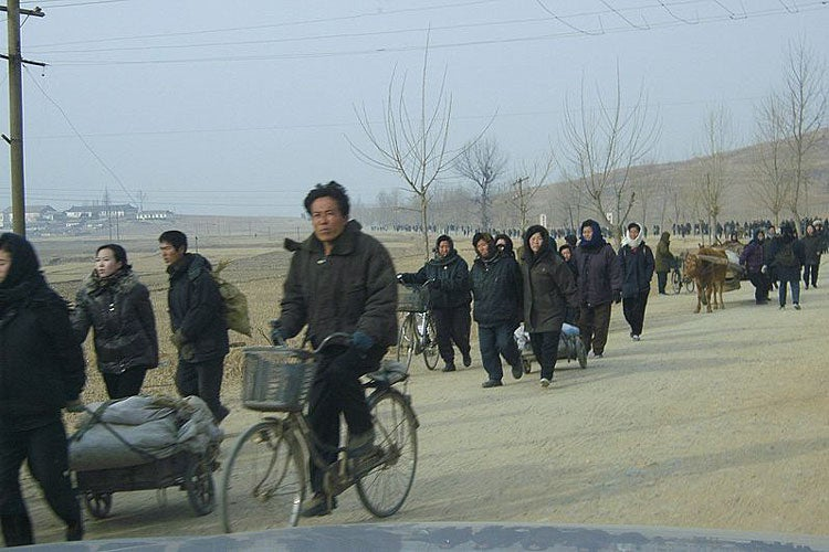 people traveling down a country road in North Korea