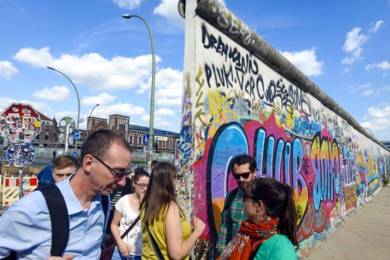 People gathered near remnants of the Berlin Wall / Paolo Bona/Shutterstock