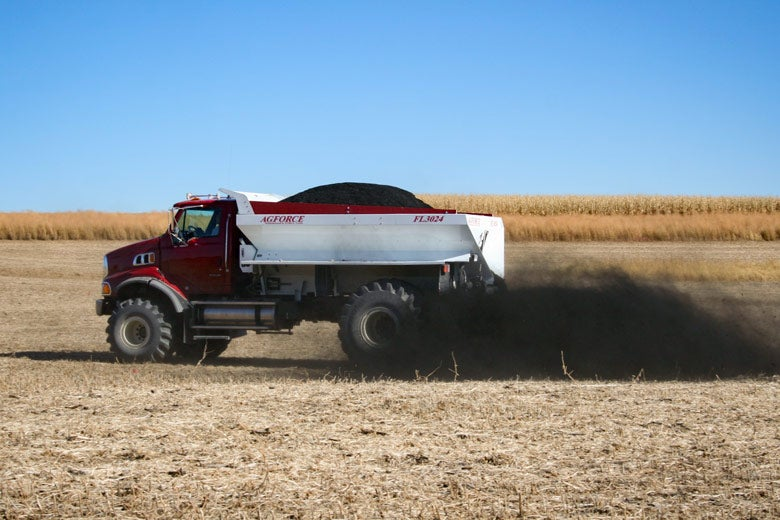 Truck spreading biochar on field