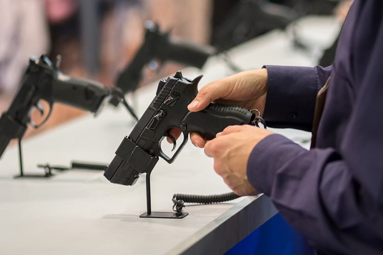hands holding a gun at display desk