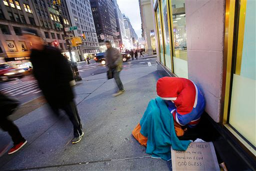homeless person huddled against cold on New York City sidewalk