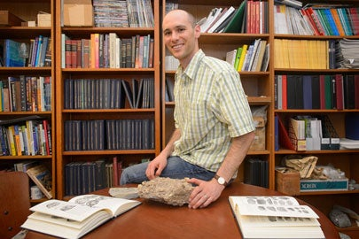 Jonathan Payne with rock infused with marine fossils / John Todd