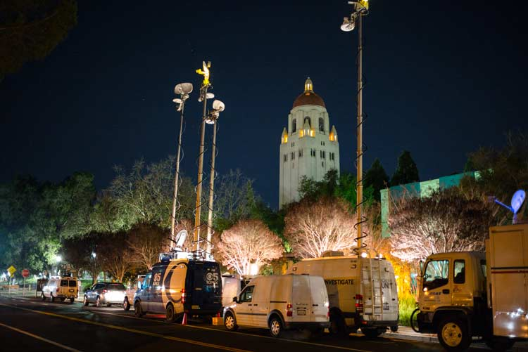Media trucks lined up along Galvez Street with Hoover tower in the background.