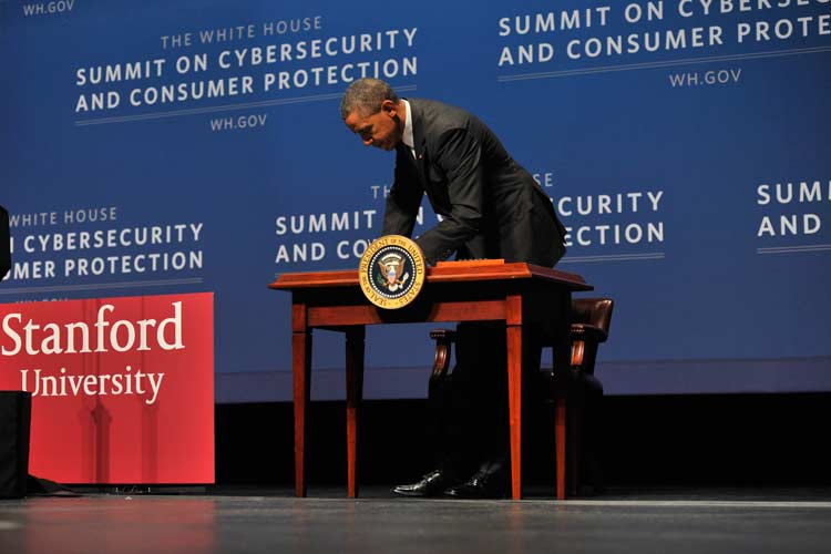 President Obama behind a table on stage signing an executive order