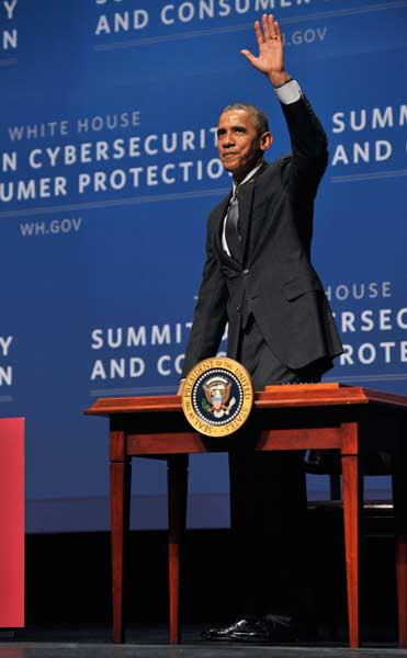 Obama standing behind a table waving to the audience.