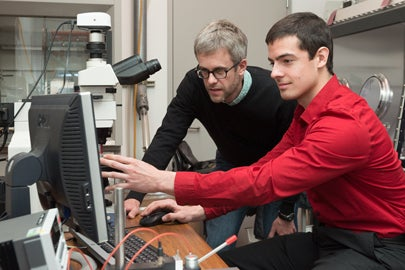 Professor Mike McGehee and graduate student Colin Bailie use a microscope to examine silver nanowires on the solar cell / L.A. Cicero