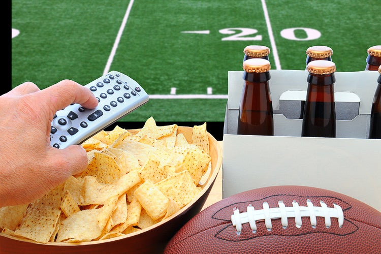 closeup of chips, beer and remote with gridiron in the background