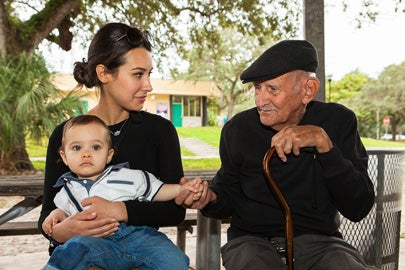 woman with child and elderly man on parkbench conversing / Fotoluminate LLC/Shutterstock