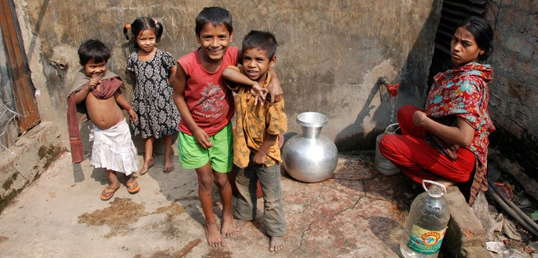 Woman and children at water standpipe in Dhaka, Bangladesh