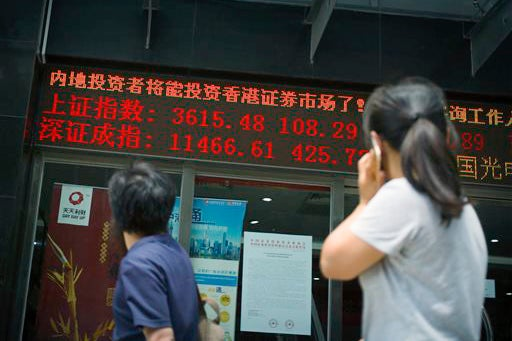 stock brokerage sign in Beijing displaying values of Shanghai and Shenzhen stock indexes / AP Photo/Mark Schiefelbein