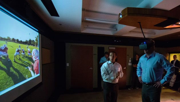 Roger Goodell wearing virtual reality headset in front of a screen with Jeremy Bailenson looking on.