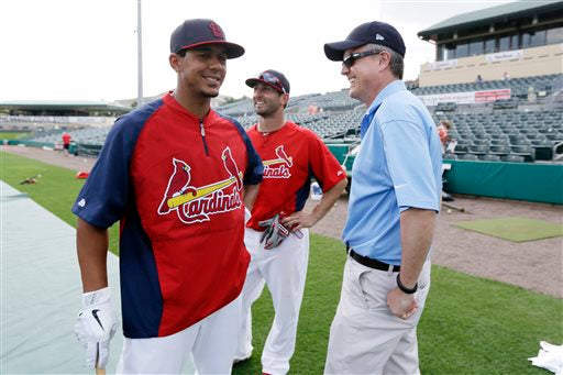 Feb. 25, 2013, file photo of Houston Astros general manager Jeff Luhnow, right, talking to St. Louis Cardinals center fielder Jon Jay, left, and second baseman Daniel Descalso