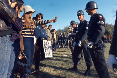 demonstrator offers flower to MP in 1967 / U.S. Army