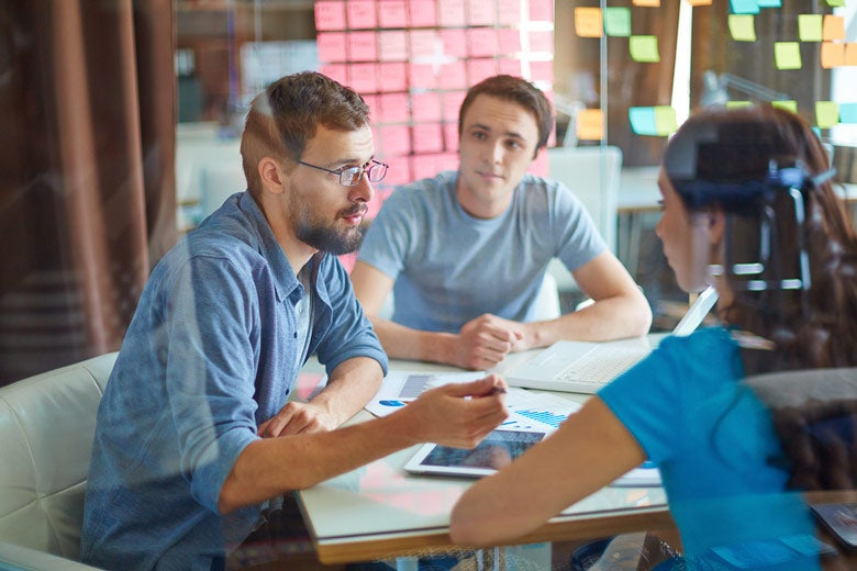 students talking around a table / Pressmaster/Shutterstock
