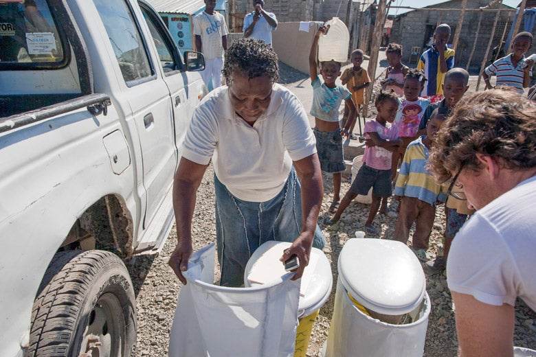 Residents of Cap Haitien, Haiti, receive portable dry household toilets