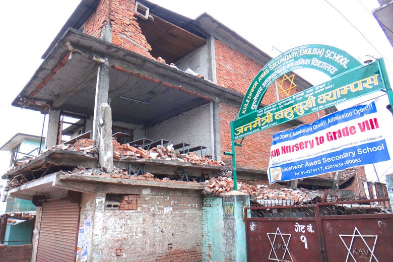 Nepali school with one of the floors visibly pancaked, other floors missing wall following April 25, 2015, earthquake