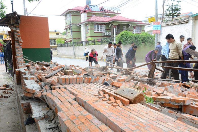 people clearing bricks from a fallen wall following April Nepal quake / Jeevan Ale