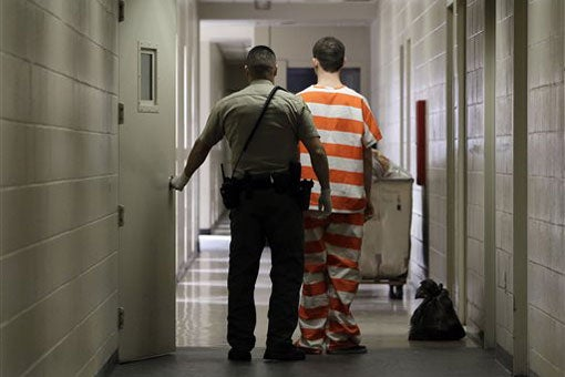 prisoner and guard walking down corridor