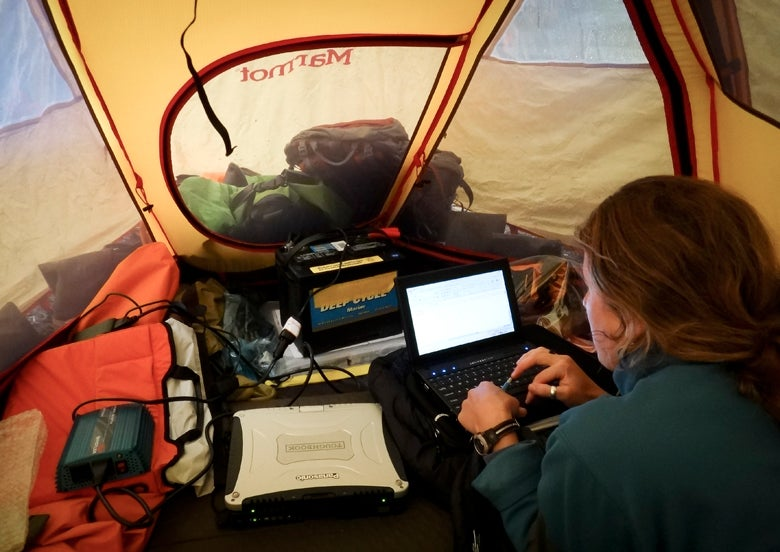 Lauren Oakes entering data in tent