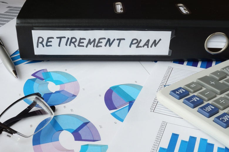 binder labeled 'retirement plan' with charts and calculator on desk