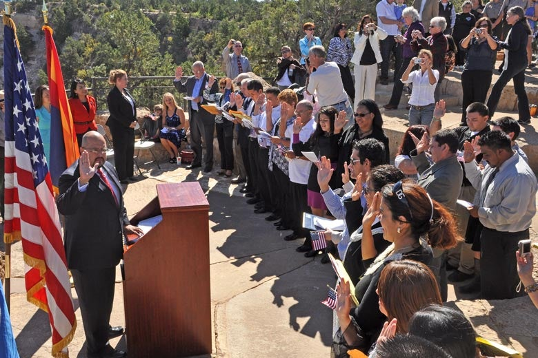 People being sworn in as U.S. citizens in an outdoor amphitheater