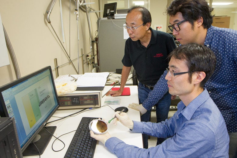 Three researchers around a computer screen