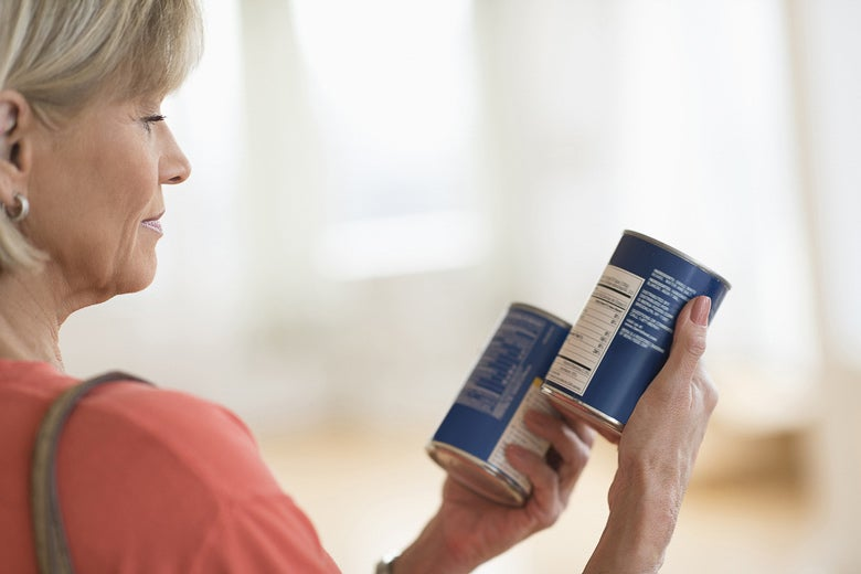 Woman reading nutritional label on a can