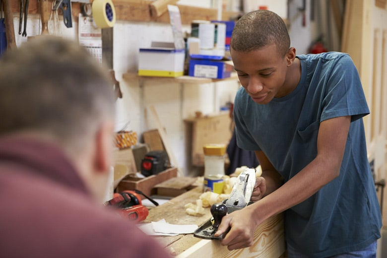 Young boy using a woodworking tool with man supervising. Photo: Monkey Business Images/Shutterstock